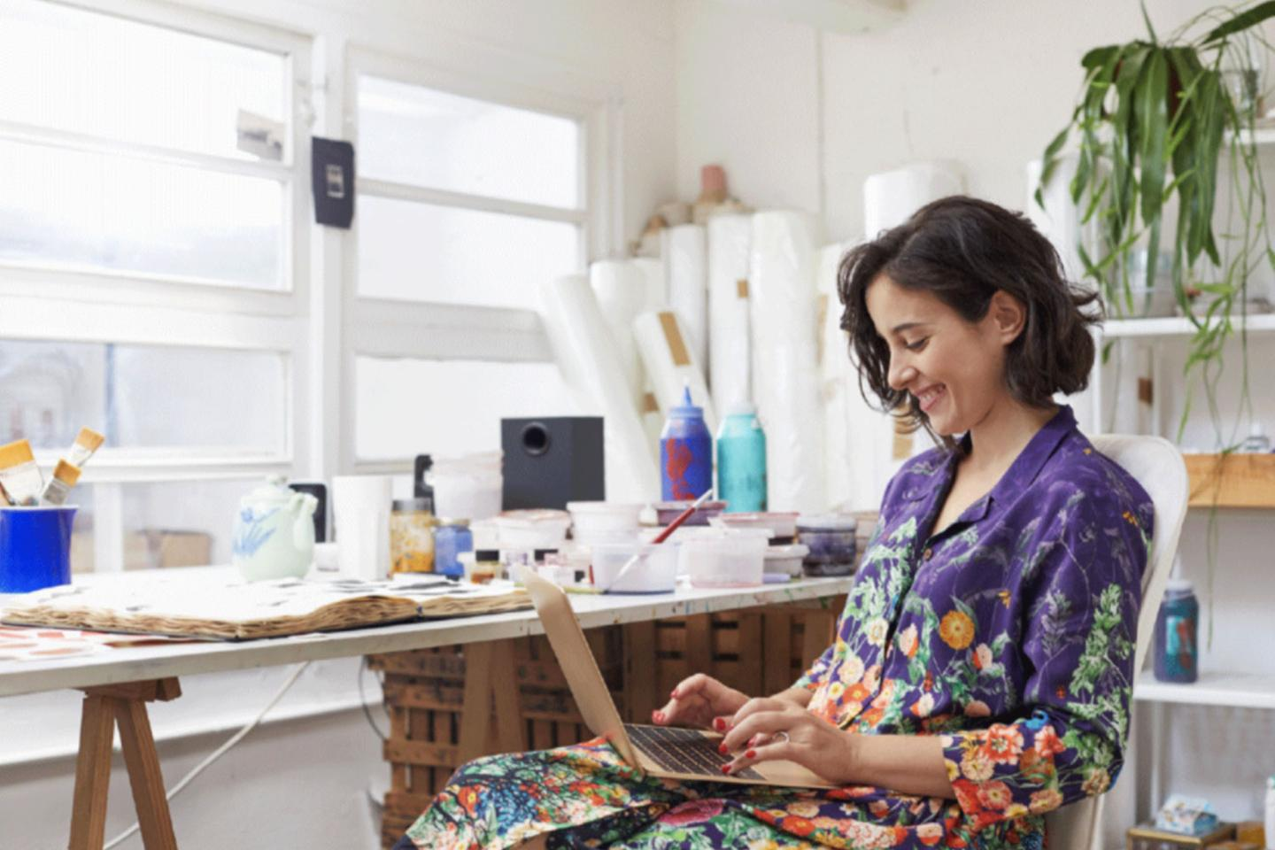 Woman in a colorful shirt happily working on her laptop