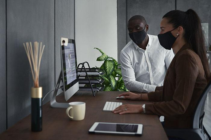 Two people looking at a laptop wearing masks